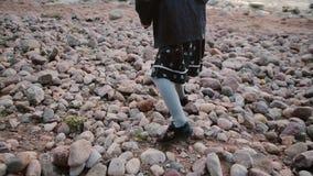 Hintere Ansicht des Mädchens, das auf das Ufer geht Kleines Mädchen, das ungewisse Schritte auf den Steinen macht stock footage