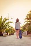 Hintere Ansicht des Mädchens mit einem Skateboard draußen an Stockfotografie