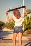 Hintere Ansicht des Mädchens mit einem Skateboard draußen an Stockbild