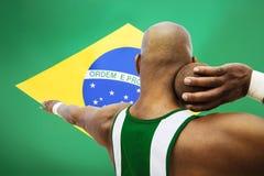 Hintere Ansicht des männlichen Schussputters, der gegen brasilianische Flagge zielt Stockfoto