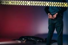 Hintere Ansicht des Mörders in den Stulpen hinter Polizeilinie lizenzfreies stockfoto