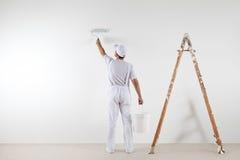 Hintere Ansicht des Malermannes die Wand, mit der Farbenrolle malend