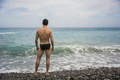 Hintere Ansicht des Mannes in den Stämmen gegen Meerblick lizenzfreie stockfotos