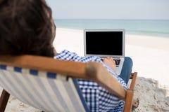 Hintere Ansicht des Mannes, der Laptop am Strand verwendet Stockbilder