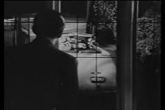 Hintere Ansicht des Mannes Fenster den Leuten heraus betrachtend, die im Auto verlassen stock footage