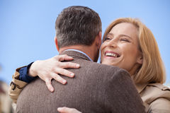 Hintere Ansicht des Mannes glückliche Frau draußen umarmend Lizenzfreie Stockfotos