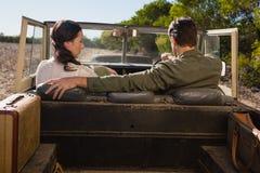 Hintere Ansicht des Mannes mit der Frau, die Straßenfahrzeug abtreibt Lizenzfreie Stockbilder