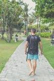 Hintere Ansicht des Mannes mit Rucksack gehend in den Strandpark von Nusa-DUA, Bali-Insel, Indonesien Stockfotografie