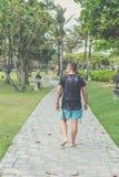 Hintere Ansicht des Mannes mit Rucksack gehend in den Strandpark von Nusa-DUA, Bali-Insel, Indonesien Lizenzfreie Stockfotografie