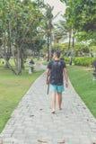 Hintere Ansicht des Mannes mit Rucksack gehend in den Strandpark von Nusa-DUA, Bali-Insel, Indonesien Stockfotos