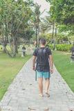 Hintere Ansicht des Mannes mit Rucksack gehend in den Strandpark von Nusa-DUA, Bali-Insel, Indonesien Lizenzfreie Stockfotos