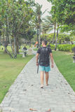 Hintere Ansicht des Mannes mit Rucksack gehend in den Strandpark von Nusa-DUA, Bali-Insel, Indonesien Stockbild
