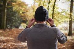 Hintere Ansicht des Mannes setzend in Kopfhörer vor Autumn Run lizenzfreie stockbilder