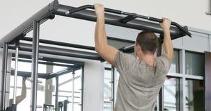 Hintere Ansicht des muskulösen Mannes im grauen T-Shirt, das Übung für Bizeps auf Barbell tut stock footage