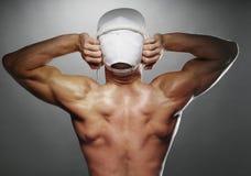 Hintere Ansicht des muskulösen Mannes mit Kappe und Kopfhörern Stockbild