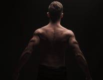 Hintere Ansicht des muskulösen Mannes seine Rückseite und Arme biegend Lizenzfreie Stockfotos