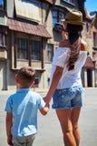 Hintere Ansicht des Mutter- und Sohnhändchenhaltens und des Machens eines Fotos O Stockbild
