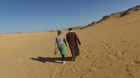 Hintere Ansicht des nubian Mannes gehend in Wüste mit weiblichem Touristen stock footage