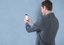 Hintere Ansicht des rührenden leeren Bildschirms des Geschäftsmannes des Handys Lizenzfreie Stockfotografie