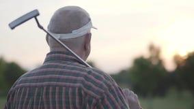 Hintere Ansicht des reifen Mannes Golf auf dem Golfplatz spielend Älterer Mann, der weg mit dem Verein auf seiner Schulter schaut stock video
