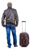 Hintere Ansicht des reisenden Mannes mit dem Koffer, der oben schaut Lizenzfreie Stockfotografie
