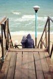 Hintere Ansicht des schönen jungen Paarhändchenhaltens, das das Meer auf den jungen Paaren des Strandes in der Liebe aufpassend u stockfoto