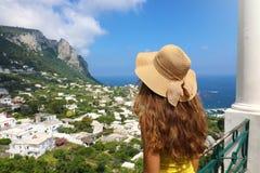 Hintere Ansicht des schönen Mädchens mit dem Strohhut, der Capri-Anblick von der Terrasse, Capri-Insel, Italien betrachtet lizenzfreie stockfotos