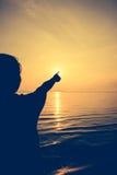 Hintere Ansicht des Schattenbildes der Frau entspannen sich an der Küste und am Zeigen auf t Stockbild