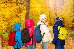 Hintere Ansicht des Schulkindhändchenhaltens in der Reihe Stockbilder