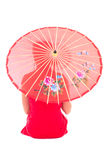 Hintere Ansicht des sitzenden Mädchens im roten Japanerkleid mit Regenschirm ist Stockfotos