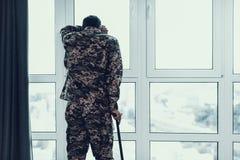Hintere Ansicht des Soldaten Leaning auf Krücke durch Fenster lizenzfreie stockfotografie