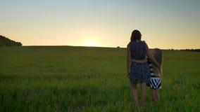 Hintere Ansicht des umarmenden und aufpassenden Sonnenuntergangs der Mutter und der kleinen blonden Tochter zusammen, stehend auf stock video footage