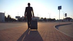 Hintere Ansicht des unerkennbaren Geschäftsmannes gehend auf Stadtstraße und Koffer auf Rädern bei Sonnenuntergang ziehend Junges stock footage