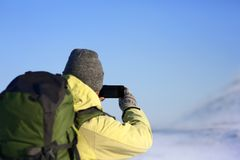 Hintere Ansicht des unerkennbaren Mannes im Hut und in Rucksack, die Foto der erstaunlichen Winterlandschaft machen Lizenzfreie Stockfotos