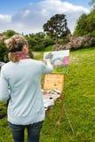 Hintere Ansicht des weiblichen Künstlers ihr Bild beendend Lizenzfreie Stockbilder