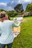 Hintere Ansicht des weiblichen Malers ihr Bild in einem Garten beendend Lizenzfreie Stockfotografie
