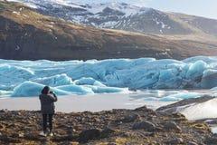 Hintere Ansicht des weiblichen Touristenphotographen, der Foto der schönen Glättungslandschaft von Skaftafell-Gletscher Vatnajoku stockbild
