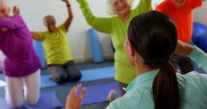 Hintere Ansicht des weiblichen Trainers ältere Leute in der Übung am Eignungsstudio 4k ausbildend stock video