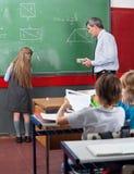 Hintere Ansicht des wenig Schulmädchen-Schreibens an Bord Lizenzfreies Stockfoto