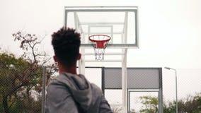 Hintere Ansicht des werfenden Balls des unerkennbaren afrikanischen Spielers in einem Basketballkorb, der Ball schlägt den Ring u stock video