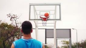 Hintere Ansicht des werfenden Balls des unerkennbaren Spielers in einem Basketballkorb, der Ball schlägt den Ring und die Ergebni stock footage