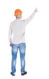 Hintere Ansicht des Zeigens des jungen Mannes im Hemd und im Sturzhelm Stockfoto