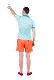 Hintere Ansicht des Zeigens von jungen Männern im T-Shirt und in den kurzen Hosen Stockbild