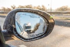 Hintere Ansicht durch gefrorenen Autoflügelspiegel auf Autobahn Lizenzfreie Stockfotografie