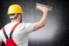 Hintere Ansicht einer Arbeitskraft, die zuhause eine Wand vergipst stockfoto