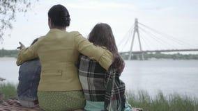 Hintere Ansicht einer eleganten reifen Frau, die auf dem Gras auf dem Riverbank, zwei nette Enkelinnen umarmend sitzt gl?cklich stock video footage