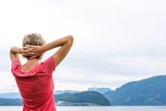 Hintere Ansicht einer Frau, die eine Ansicht in Fjord genießt Stockfotos