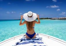 Hintere Ansicht einer Frau, die eine Bootsfahrt in den Malediven genießt stockfotografie