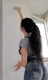 Hintere Ansicht einer Frau, die eine Wand malt Lizenzfreie Stockfotos