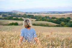 Hintere Ansicht einer Frau, die im trockenen unfruchtbaren Gras, schauend im Horizont sitzt stockbild